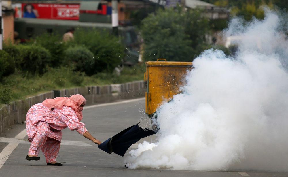 امرأة تحاول ابعاد قنبلة غاز مسيل للدموع خلال التصادمات مع الشرطة في كشمير، 17 أغسطس/ آب 2016