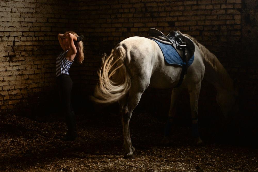 رياضية روسية وخيلها بعد الانتهاء من تدريبات ركوب الخيل في نوفوسيبيرسك