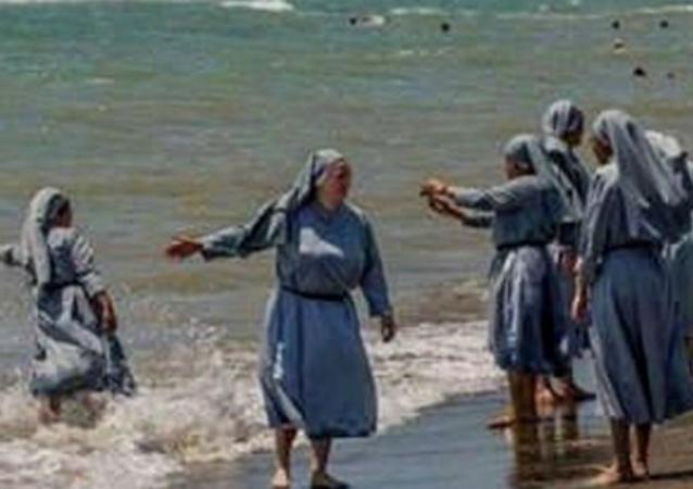 صورة لراهبات مسيحيات يلهون على شاطئ البحر بلباسهن الديني