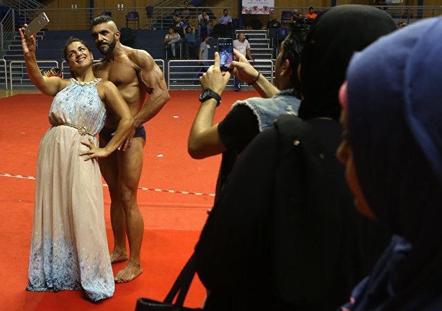 فتاة تأخذ صورة سيلفي مع أحد المشاركين في مسابقة كمال الأجسام ببيروت