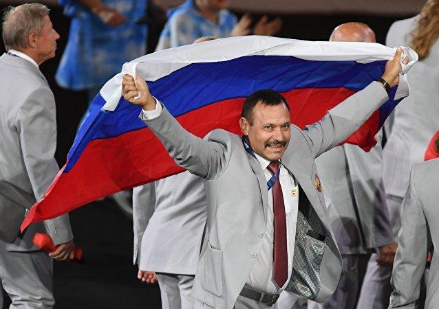 مدير المركز الجمهوري لتدريبات الألعاب الأولمبيية لألعاب القوى أندريه فوموتشكين يرفع علم روسيا خلال سير موكب الرياضيين وأعضاء الوفود الوطنية في حفل افتتاح الألعاب الأولمبية للمعاقين الصيفية، الخامس عشر لعام 2016 في ريو دي جانيرو.