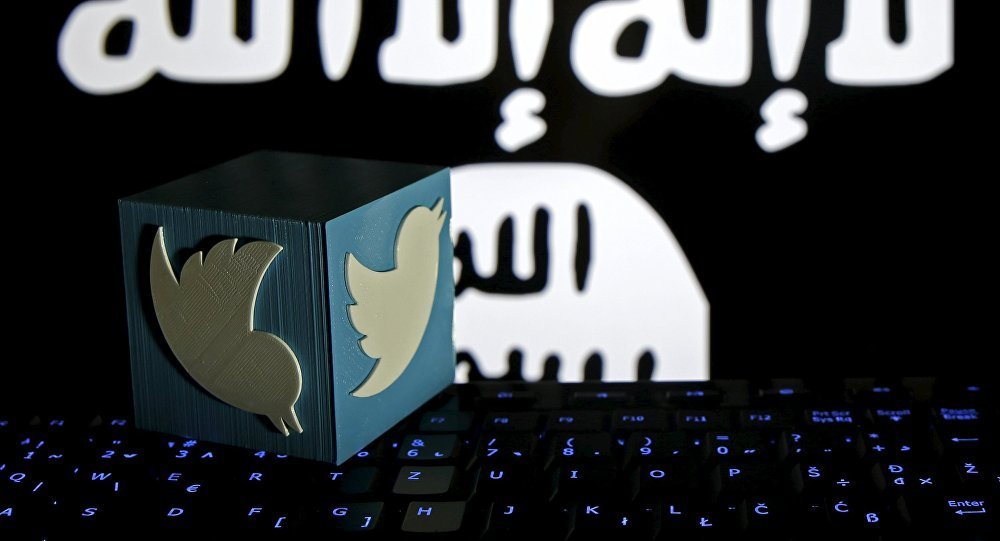 يظهر على الصورة شعار تويتر وفي الخلفية علم منظمة داعش الإرهابية