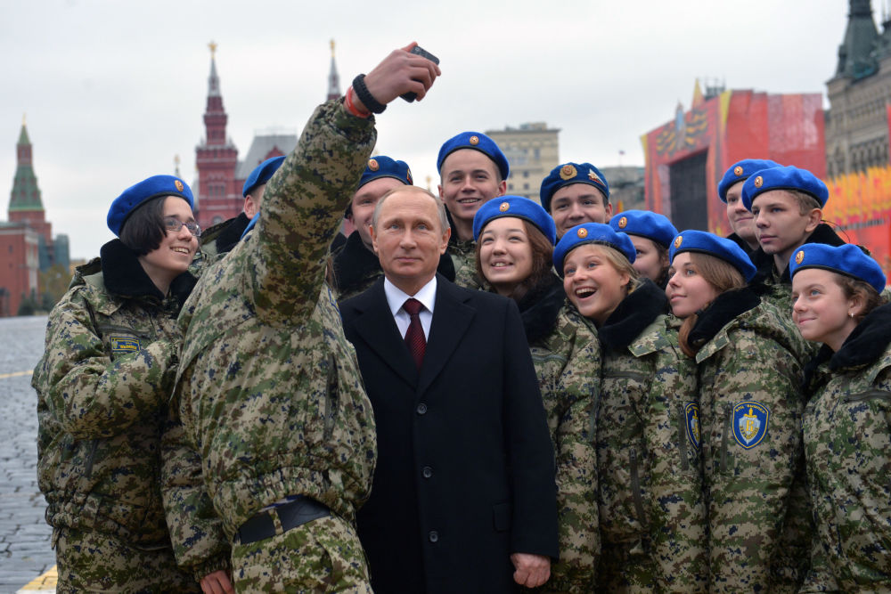 الرئيس الروسي فلاديمير بوتين يلتقط صورة سيلفي جماعية مع أفراد المركز الحربي الوطني فيمبل خلال مراسم وضع أكاليل الزهور أمام تمثال كوزما مينين ودميتري بوجاركس على الساحة الحمراء