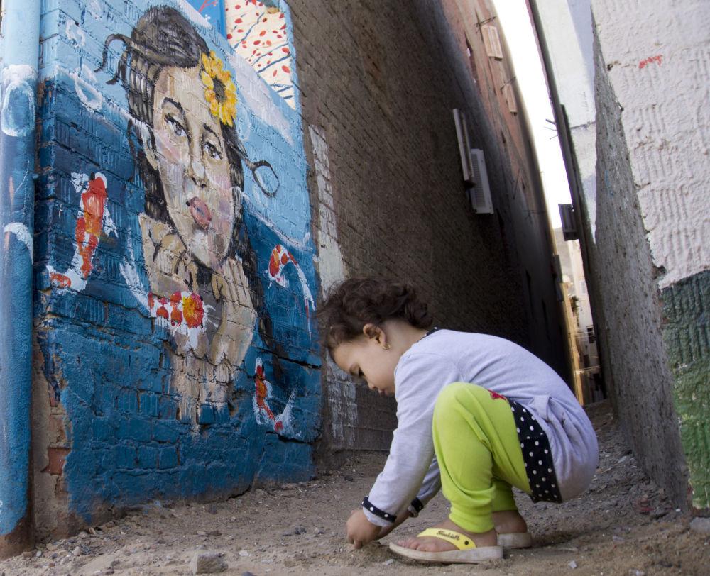 طفلة تلعب خلال معرض اللوحات الفنية في برلس
