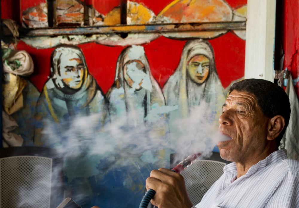 رجل يدخن ووراءه معرض اللوحات الفنية