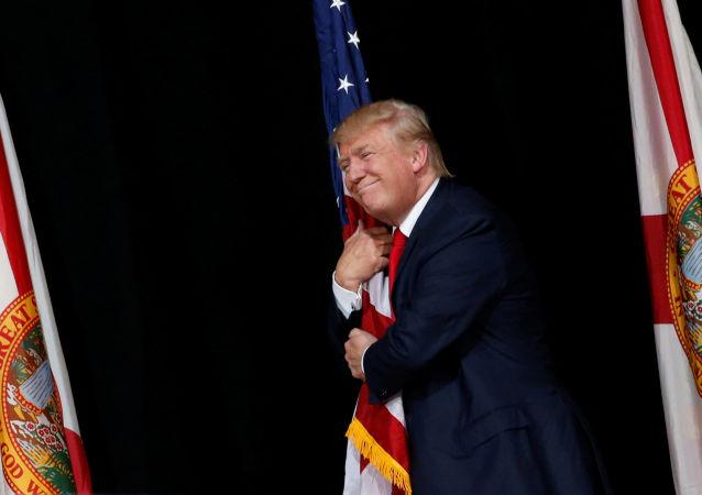 المرشح للانتخابات الرئاسية الأمريكية عن الحزب الجمهوري دونالد ترامب يحتضن علم الولا يات الأمريكية، 24 أكتوبر/ تشرين الأول 2016