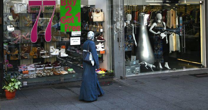 امرأة تسير بجوار محل تجاري في مدينة بيروت