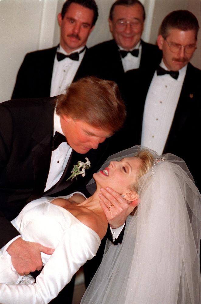 المرشح للانتخابات الرئاسية من الحزب الجمهوري دونالد ترامب يقبّل عروسته مارلا أمام كاميرات الصحافيين بفندق نيويورك بلازا أوتيل، 20 ديسمبر/ كانون الأول 1992