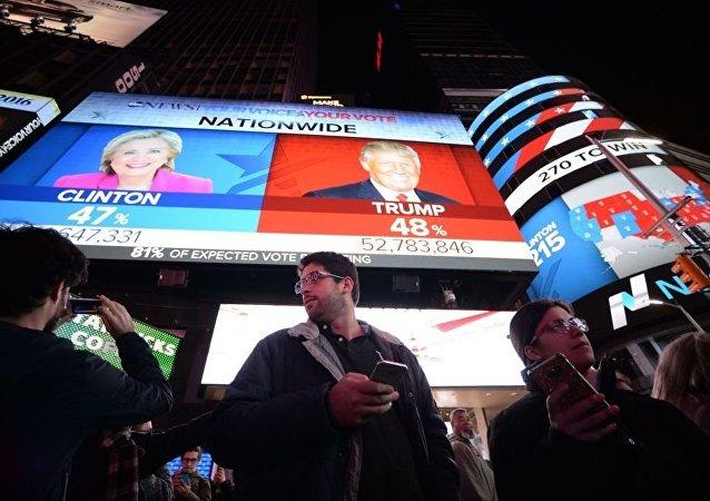 أشخاص يقفون على خلفية شاشة تظهر النتائج الأولية للتصويت في الانتخابات الرئاسية الأمريكية في ساحة تايمس سكوير، نيويورك 8 نوفمبر/ تشرين الثاني 2016