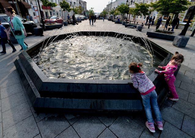 أطفال يلعبون بجوار نافورة مياه وسط مدينة فلاديفوستوك.