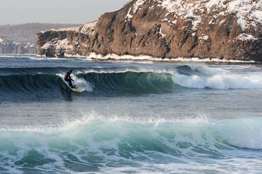 رجل يمارس رياضة ركوب الأمواج شتاءً في خليج أوسوريسك بجزيرة روسكي.