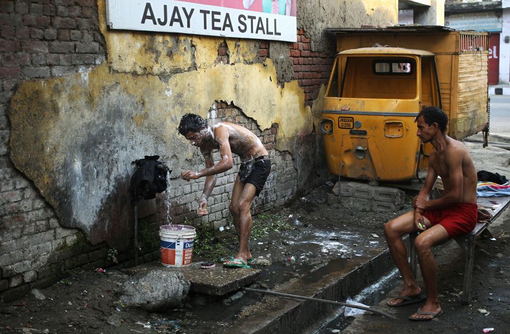رجل يستحم في  أحد شوارع مدينة جامو، الهند 22 نوفمبر/ تشرين الثاني 2016