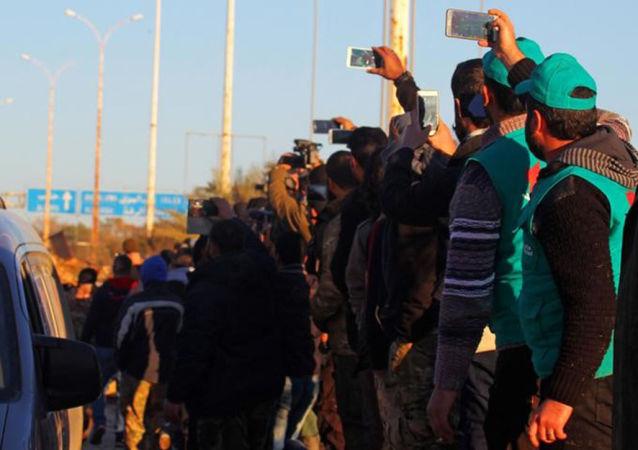 سوريون في حلب يشاهدون مغادرة الحافلات الخضراء التي تنقل المسلحين وأفراد أسرهم، 15 ديسمبر/ كانون الأول 2016