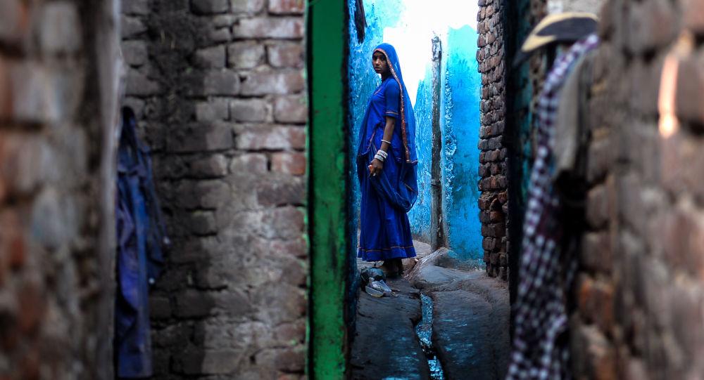 امرأة هندية تسير بجوار منزلها في نيو دلهي، الهند 20 ديسمبر/ كانون الأول 2016