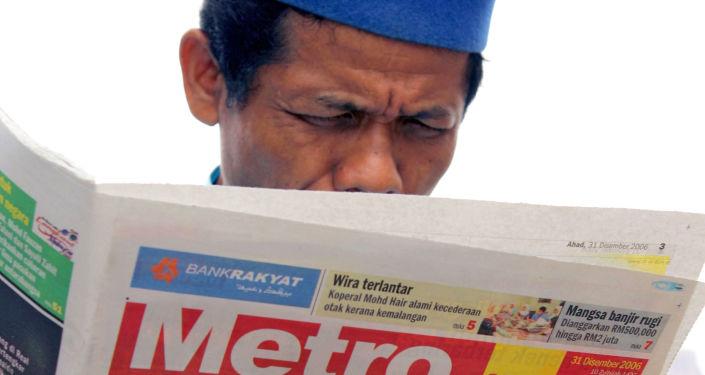 رجل يقرأ نبأ إعدام الرئيس العراقي السابق صدام حسين في كوالا لمبور، 31 ديسمبر/ كانون الأول 2006