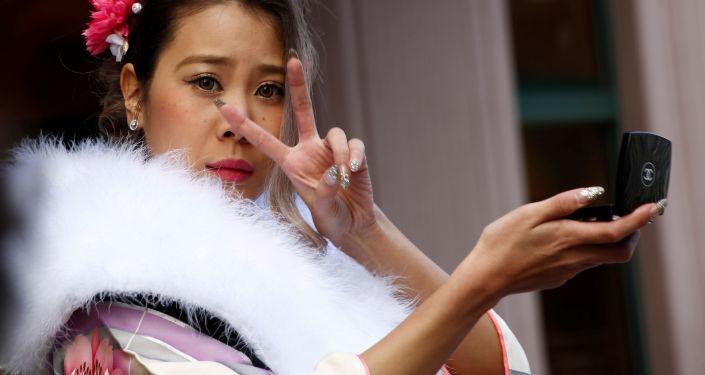 فتاة يابانية ترتدي الزي التقليدي الياباني كيمونو تمسك بمرآتها وتعدّل على المكياج، اليابان 9 يناير/ كانشون الثاني 2017