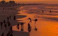 مواطنون فلسطينيون على شاطئ البحر في مدينة غزة خلال غروب الشمس، قطاع غزة، فلسطين 10 يناير/ كانون الثاني 2017