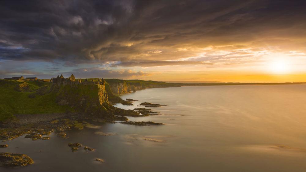 سحب فوق قلعة دانليوس، إرلندا الشمالية - للمصور رشيد خايدانوف المشارك في مسابقة National Geographic Traveller-2017