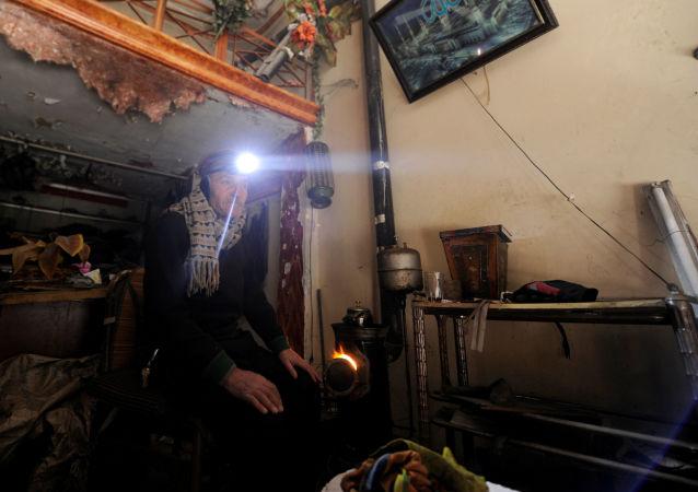 رجل يجلس بجوار نار للتدفئة في حلب، سوريا 30 يناير/ كانون الثاني 2017