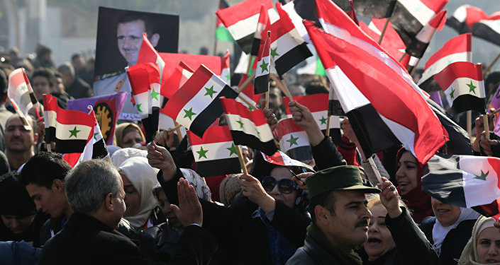سوريون يحملون صور الرئيس بشار الأسد وأعلام سوريا في حلب