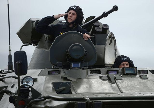 جندي يطل من المدرعة العسكرية ب.ت.ار-82أ خلال البروفة العامة للعرض العسكري بمناسبة إحياء الذكرى الـ 71 لعيد النصر، في القاعدة العسكرية حميميم في سوريا.