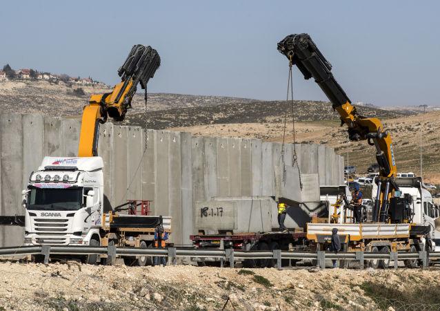 عمال يشيدون جزءاً جديداً من الجدار الفاصل على طول كيبوتس كراميم بمدينة الخليل في جنوب الضفة الغربية، 7 فبراير/ شباط 2017