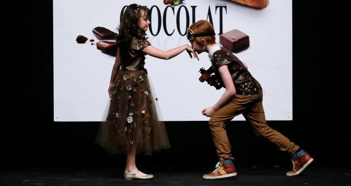 أطفال يرتدون أزياء مصنوعة من الشوكولاته في معرض للشوكولاتة - لو صالون دو شوكولا (Le Salon du Chocolat - Chocoladesalon) في بروكسل، بلجيكا 9 فبراير/ شباط 2017.