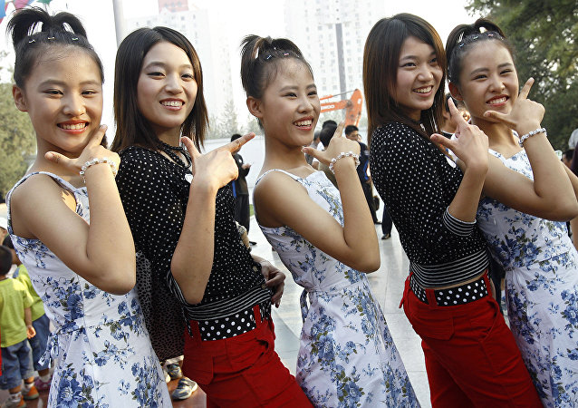 The Li sisters, a trio of 15-year-old triplets from Beijing pose for a photo with a pair of twins during the 2006 Beijing Twins Days Festival