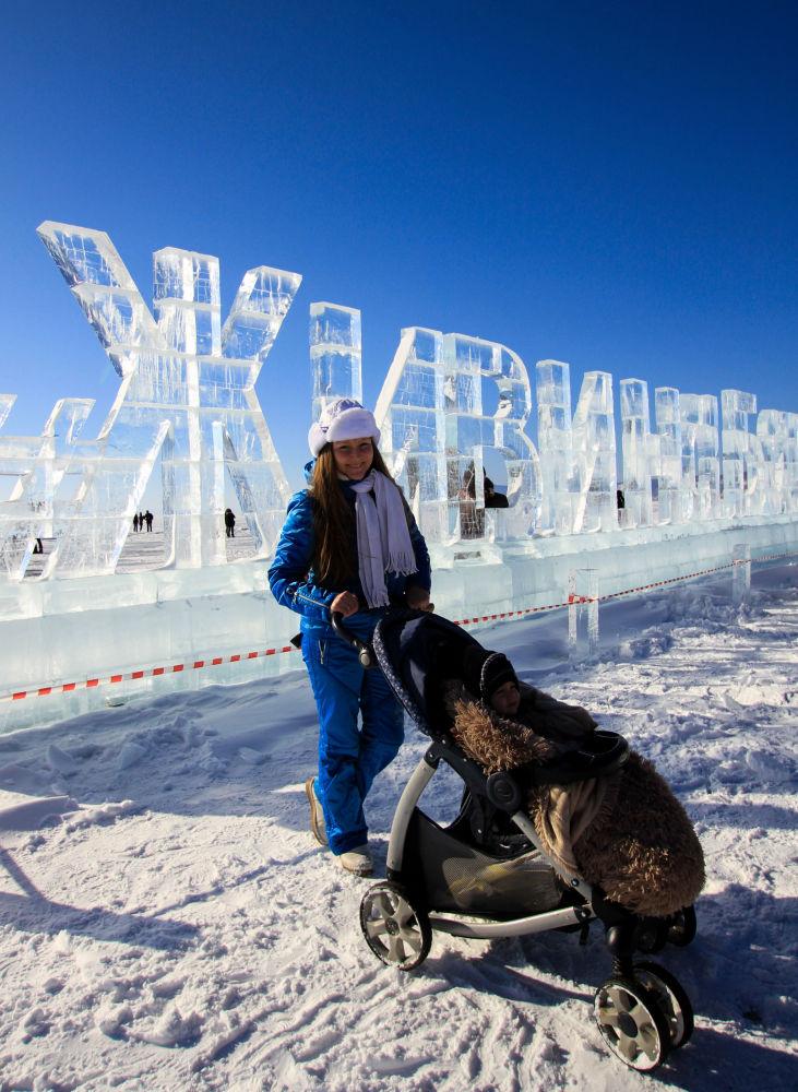 امرأة وطفلها في مهرجان للألعاب الشتوية زيمنيادا-2017 تلتقط صورة على خلفية جملة محفورة من الثلج عِش في بايكال في إقليم إركوتسك.