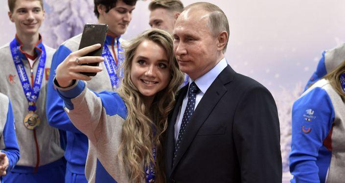 رئيس روسيا فلاديمير بوتين يلتقط صورة سيلفي مع أبطال المسابقة الرياضية للألعاب الشتوية قي كراسنويارسك
