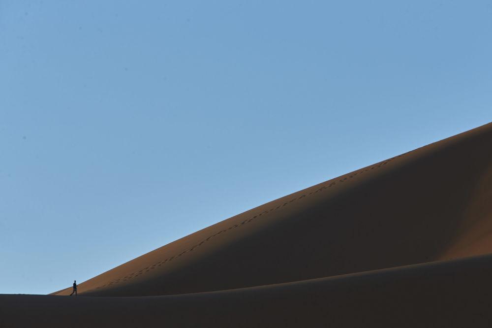 سائح يتسلق التل لمشاهدة شروق الشمس في مرزوقة، على طول طريق يسمى بـ طريق ألف قلعة في جبال الأطلس، المغرب 5 مارس/ آذار 2017.