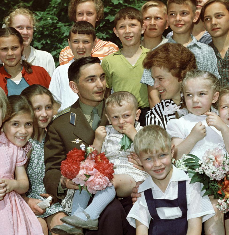 رائدة الفضاء فالنتينا تيريشكوفا ورائد الفضاء فاليري بيكوفسكي يجلسون وسط أطفال بعد عودتهما من رحلة الفضاء