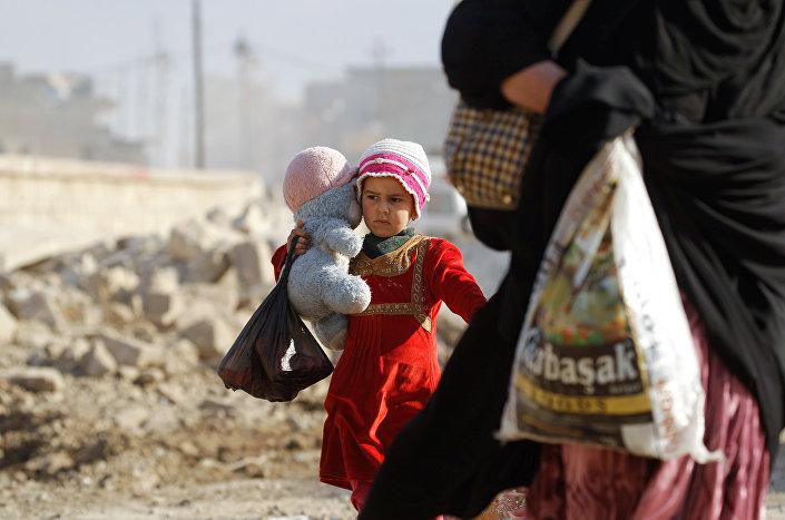طفلة تحمل لعبتها وتهرب من الموصل