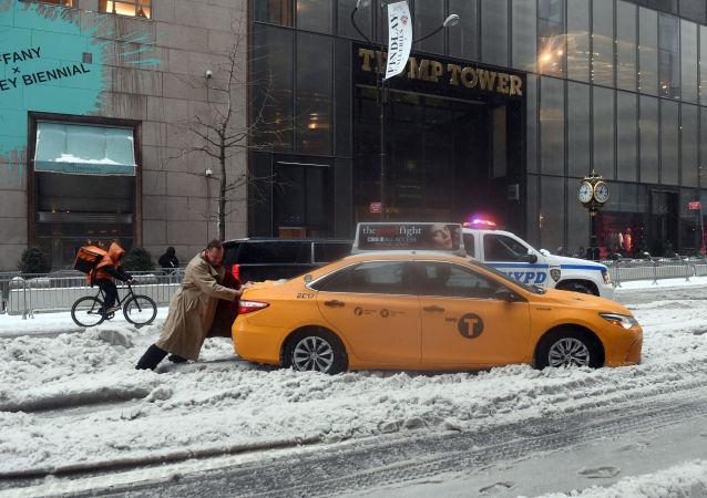 راكب سيارة أجرة في مدينة نيويورك يحاول دفع السيارة من مكانها، نيويورك 14 مارس/ آذار 2017