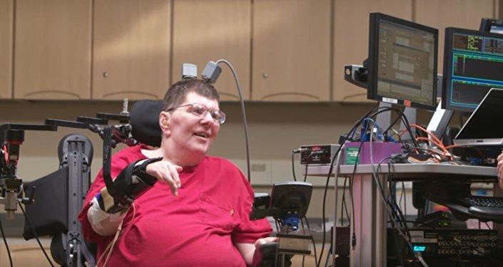 رجل مشلول يستخدم الأفكار لتحريك الذراع و اليدين