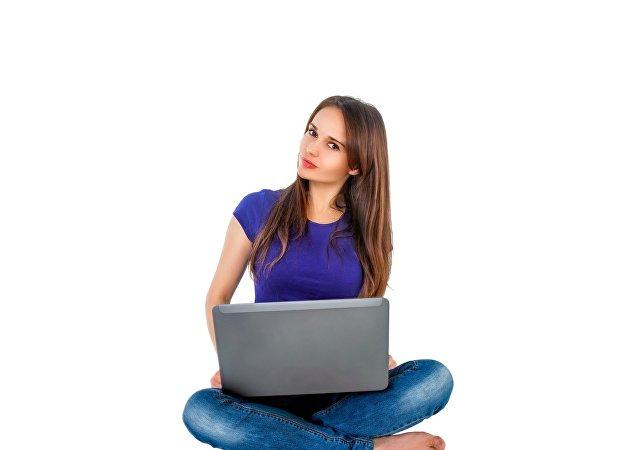 فتاة تعمل على حاسب محمول