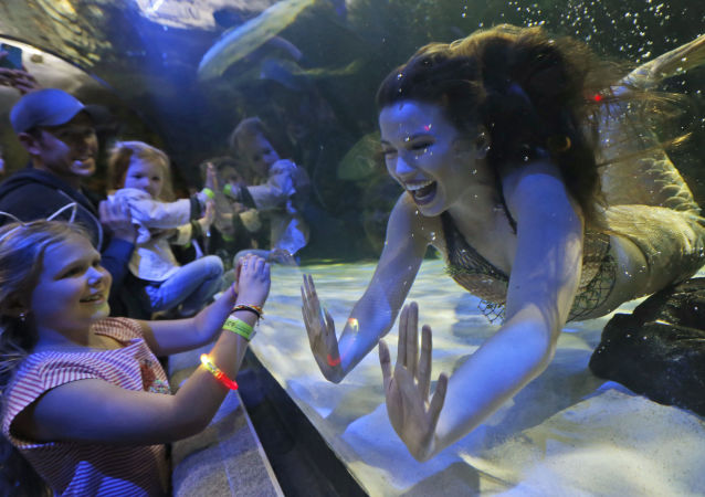فتاة-حورية، هايلس بارسيلس تحيي أطفالاً في حديقة فرجينيا أكواريوم (حوض أسماك كبير)في فرجينيا، الولايات المتحدة 3 أبريل/ نيسان 2017