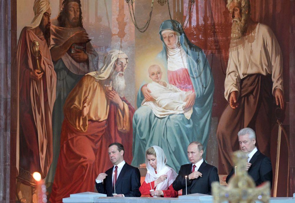 الرئيس الروسي فلاديمير بوتين، ورئيس الوزراء الروسي دميتري مدفيديف وزوجته سفيتلانا مدفيديفا، ورئيس بلدية موسكو سيرغي سوبيانين، أثناء مراسم الاحتفال بعيد الفصح المجيد في كتدرائية المسيح المخلص في موسكو، روسيا 15 أبريل/ نيسان 2017