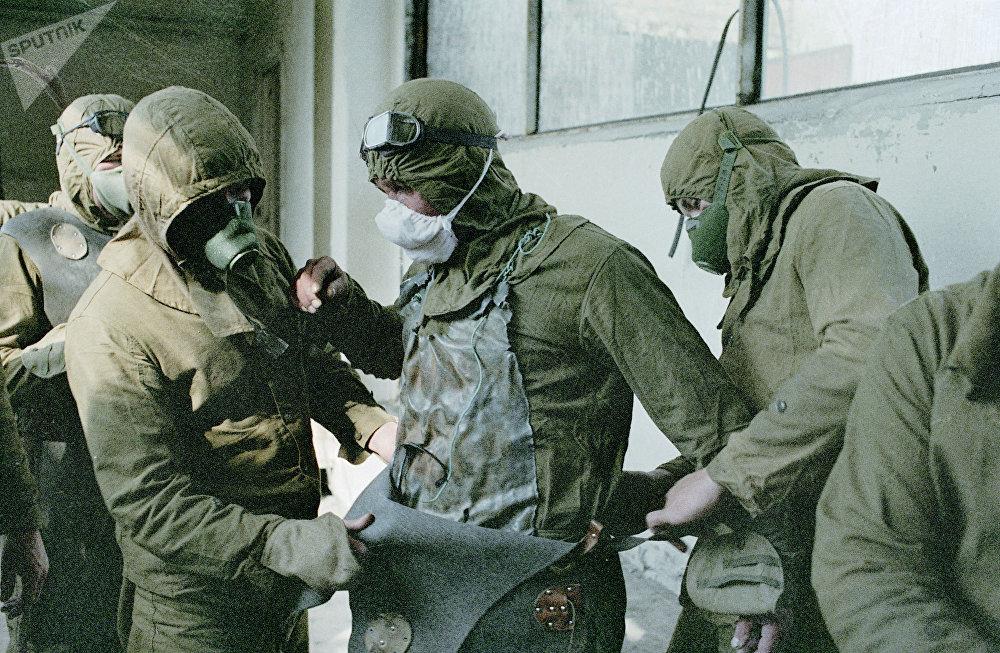 كارثة تشيرنوبيل - أشخاص يرتدون زيا واقيا قبل العمل على إزالة الأجزاء التالفة من سقف المفاعل الذري لمحطة تشيرنوبيل
