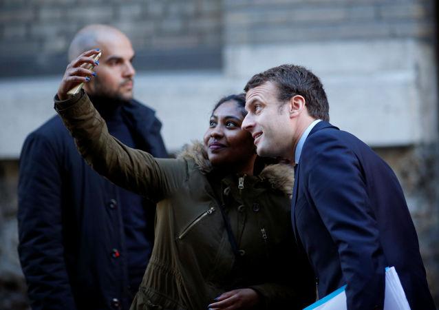 فتاة تلتقط صورة سيلفي مع المرشح للانتخابات الرئاسية الفرنسية إيمانويل ماكرون في باريس، فرنسا 2 مايو/ آيار 2017