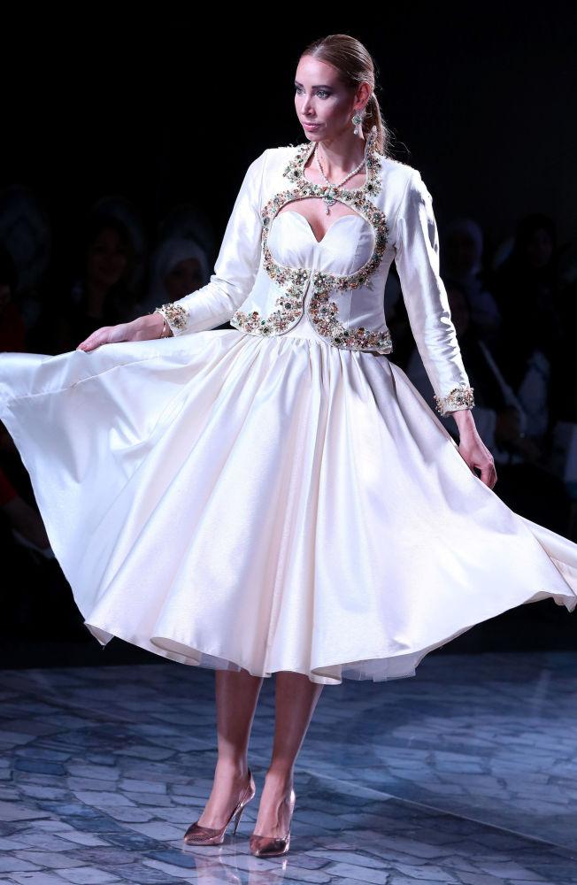 Альт: عارضة أزياء تقدّم زياً من تصميم الجزائري كريم أكروف خلال عرض أسبوع الموضة في الكويت، 8 مايو/ آيار 2017