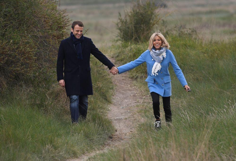 المرشح للانتخابات الرئاسية الفرنسية إيمانويل ماكرون وزوجته بريدجيت خلال سيرهما معاً في لو توكيت شمال فرنسا، عشية الدورة الأولى من الحملة الدعائية للانتخابات الرئاسية، 22 أبريل/ نيسان 2017