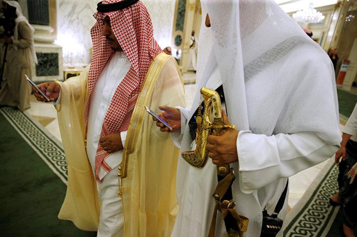 مسؤولان سعوديان يتفقدان الهاتف في أثناء زيارة ترامب