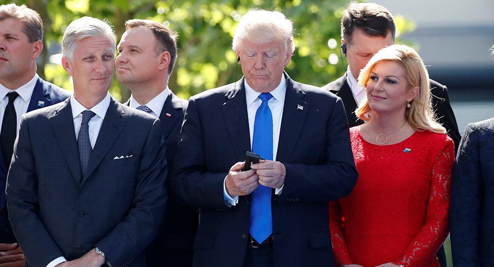 ترامب يتحدث في هاتفه لحظة انطلاق أعمال قمة الناتو