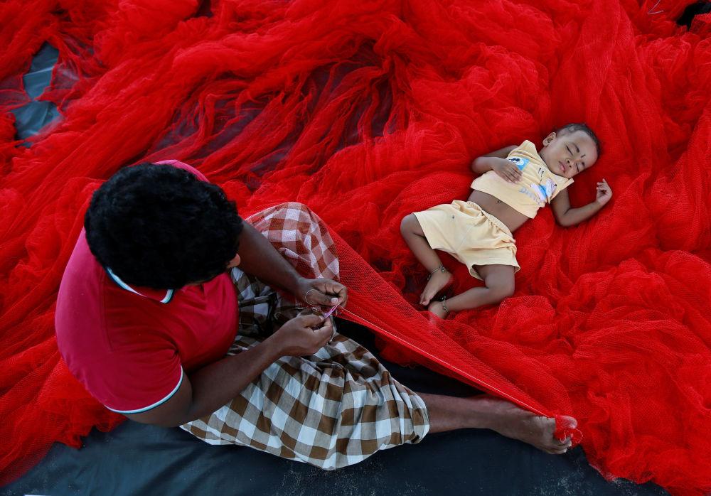 طفل هندي ينام على شبكة صيد في كوتشي، الهند 23 مايو/ آيار 2017