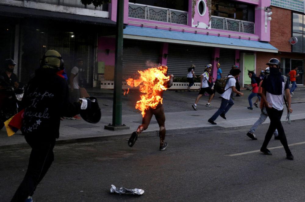 نيران تشتعل في أحد المتظاهرين خلال الاحتجاجات ضد حكومة الرئيس نيكولاس مادورو في العاصمة كاراكس، فنزويلا 20 مايو/ آيار 2017
