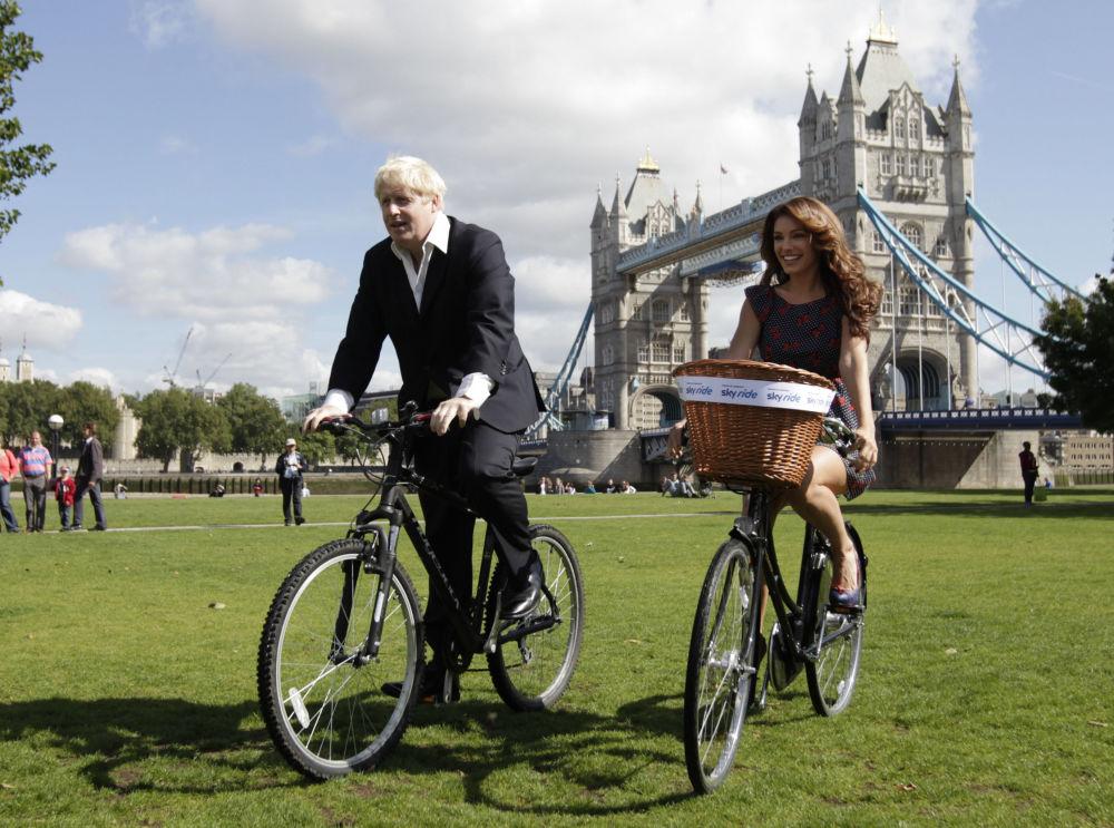 رئيس بلدية لندن (حينئذ) بوريس جونسون يركب دراجته برفقة كيلي بروك في لندن، 31 أغسطس/ آب 2010