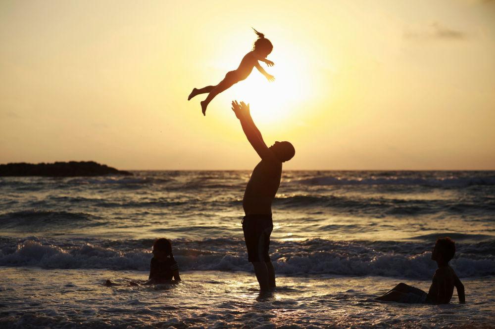 رجل يلعب مع طفلته على شاطئ البحر