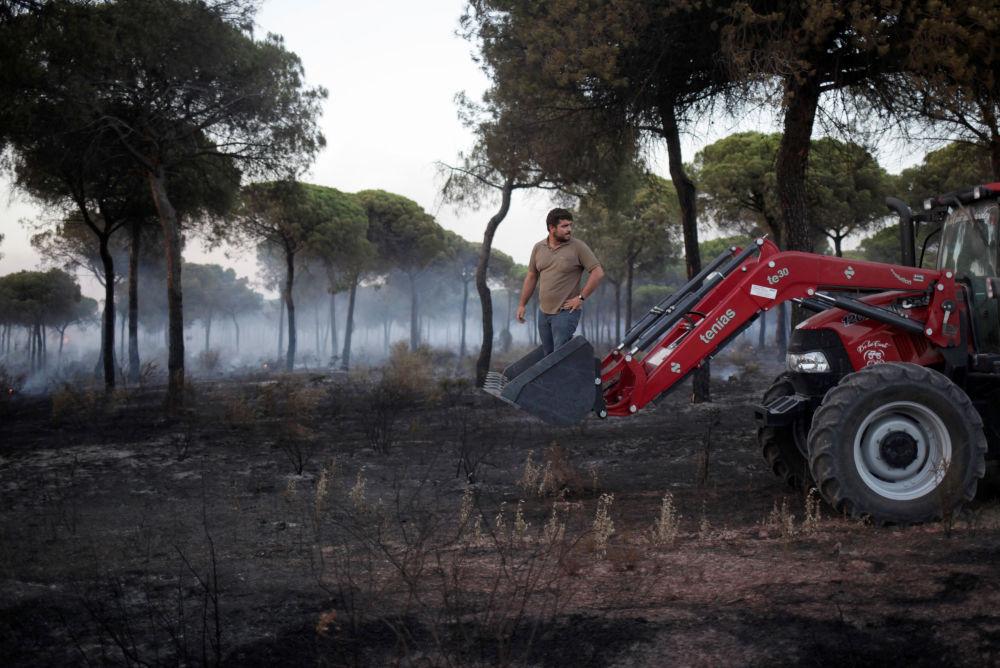 رجل يساعد بإطفاء الحرائق في جنوب إسبانيا