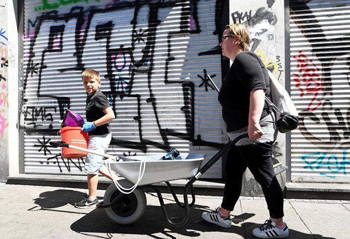 طفل يقوم بتنظيف الشارع مع والدته